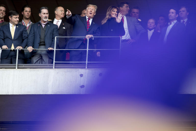 President Donald Trump and first lady Melania Trump stand to salute the troops at a halftime event during an NCAA college football game between LSU and Alabama at Bryant-Denny Stadium, in Tuscaloosa, Ala., Saturday, Nov. 9, 2019. (AP Photo/Andrew Harnik)