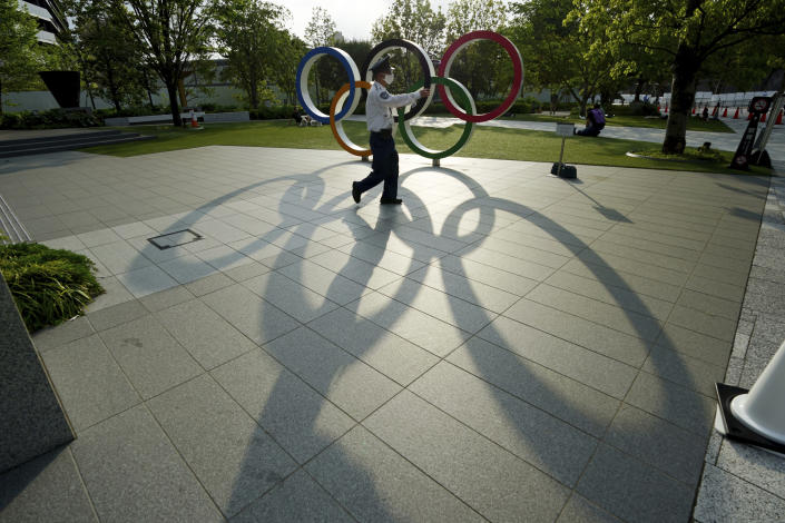 A security guard wearing a protective mask to help curb the spread of the coronavirus walks in front of the Olympic Rings on May 9, 2021, in Tokyo. The Japanese government was quick to respond on Tuesday, May 25, 2021 to U.S. travel warning for Americans against traveling to Japan and denied impact on Olympic participants, as the country determinedly prepare to host the postponed games in two months. (AP Photo/Eugene Hoshiko)