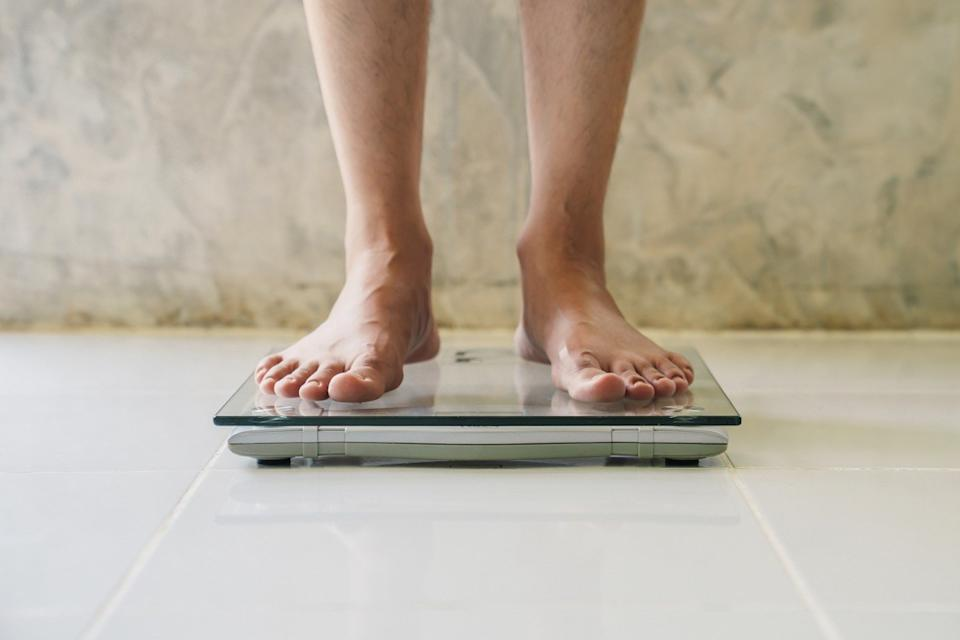 Man weighing himself on scale