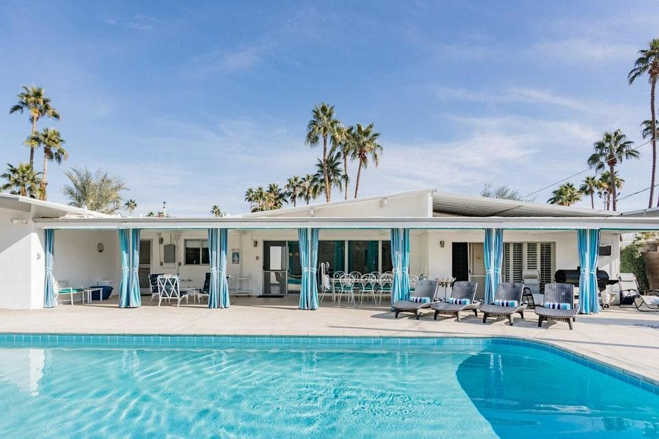 """<p><a href=""""https://www.cntraveler.com/story/how-safe-are-hotel-pools-this-summer?mbid=synd_yahoo_rss"""" rel=""""nofollow noopener"""" target=""""_blank"""" data-ylk=""""slk:A pool"""" class=""""link rapid-noclick-resp"""">A pool</a> is must come summer, and in Palm Springs, you can take a dip year round. We suspect you'll be spending lots of time around the centerpiece of this mid-century desert home, either splashing in the water or sitting under the shade in one of the many outdoor lounge chair options. Two of the four bedrooms, as well as the living room, lead out to the back patio and pool through sliding glass doors. It's worth noting that the house is definitely best suited to families—one bedroom has two king-size beds, and the fourth bedroom is really a sectioned off portion of another bedroom. Still, there is plenty of room for up to eight guests, darkening shades for a good night's sleep, air conditioning, and a dishwasher and washing machine, among other amenities.</p> <p><strong>Book now:</strong> <a href=""""https://airbnb.pvxt.net/PP7gR"""" rel=""""nofollow noopener"""" target=""""_blank"""" data-ylk=""""slk:From $672 per night or $5,396 per month, airbnb.com"""" class=""""link rapid-noclick-resp"""">From $672 per night or $5,396 per month, airbnb.com</a></p>"""