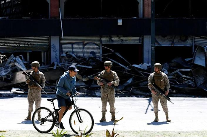 Soldiers patrol the street one day after a protest against the government in Valparaiso