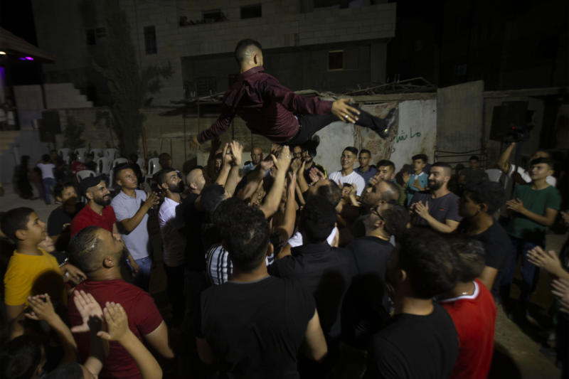 A Palestinian groom is thrown in the air during a wedding party in Azmut near the West Bank city of Nablus, Thursday, Sept. 24, 2020. In a region where marriage is the cornerstone of society, couples are plowing ahead with weddings, despite the deadly risks. From the Palestinian territories to the United Arab Emirates, officials attribute a spike in coronavirus cases to traditional, large-scale weddings that flout public health restrictions. (AP Photo/Majdi Mohammed)