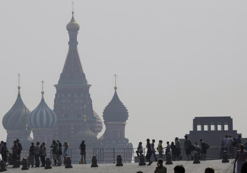 FILE - In this July 29, 2010 file photo, Moscow's St. Bazil's Cathedral, background, is seen through a smog covering Moscow during a heat wave. The mausoleum of Vladimir Lenin  is at right. The excessive amount of extreme weather that dominated 2010 is a classic sign of man-made global warming that climate scientists have long warned about. They calculate that the killer Russian heat wave, setting a national record of 111F (nearly 44 C), would happen once every 100,000 years without global warming. (AP Photo/Misha Japaridze, File)