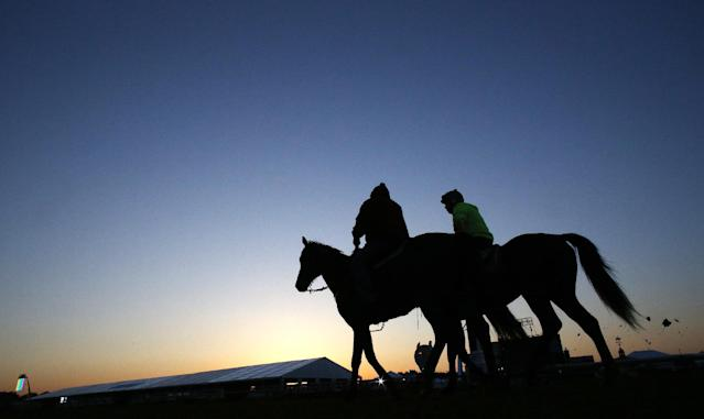 Preakness Stakes entrant Kid Cruz with exercise rider Reul Munoz moves on the track with an outrider before the 139th Preakness Stakes horse race at Pimlico Race Course, Saturday, May 17, 2014, in Baltimore. (AP Photo/Matt Slocum)