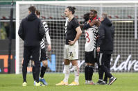 Manchester United's Paul Pogba, second right, embraces teammate Juan Mata following the Europa League round of 16 second leg soccer match between AC Milan and Manchester United at the San Siro Stadium, in Milan, Italy, Thursday, March 18, 2021. (AP Photo/Antonio Calanni)