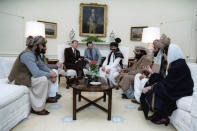 """FILE - In this photo courtesy Ronald Reagan Library, then President Ronald Reagan meets with Afghan """"freedom fighters"""" on Feb. 2, 1983, in the Oval Office of the White House in Washington, to discuss Soviet atrocities in Afghanistan. The former Soviet Union marched into Afghanistan on Christmas Eve, 1979, claiming it was invited by the new Afghan communist leader, Babrak Karmal, setting the country on a path of 40 years of seemingly endless wars and conflict. After the Soviets left in humiliation, America was the next great power to wade in. (Courtesy Ronald Reagan Library via AP)"""