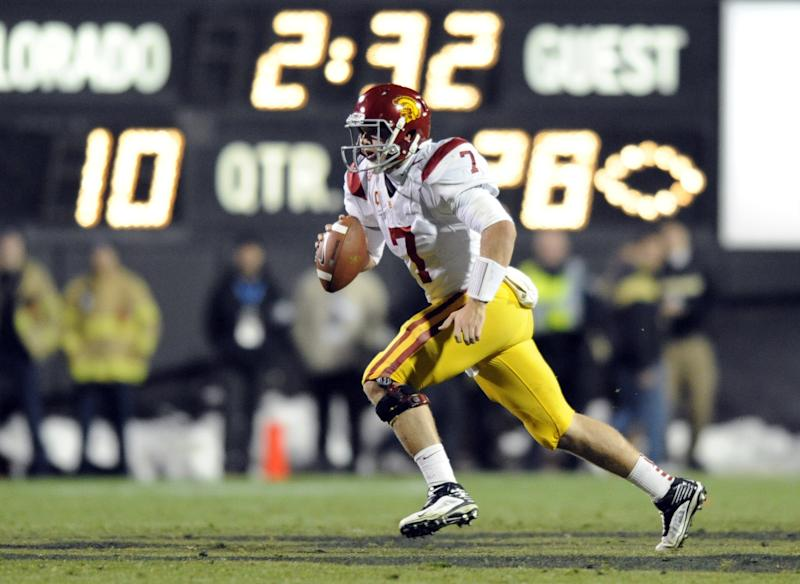 FILE- In this Nov. 4, 2011, file photo, Southern California quarterback Matt Barkley (7) scrambles against Colorado during the second half of an NCAA college football game in Boulder, Colo. Barkley skipped the NFL for the chance at a national title. (AP Photo/Jack Dempsey, File)
