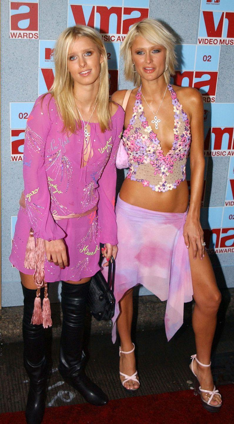 <p>The socialite sisters matched in pink looks for the 2002 VMAs. Nicky wore a long-sleeved tunic with black thigh-high boots, while Paris slipped into a floral halter top with a napkin-hemmed skirt.</p>