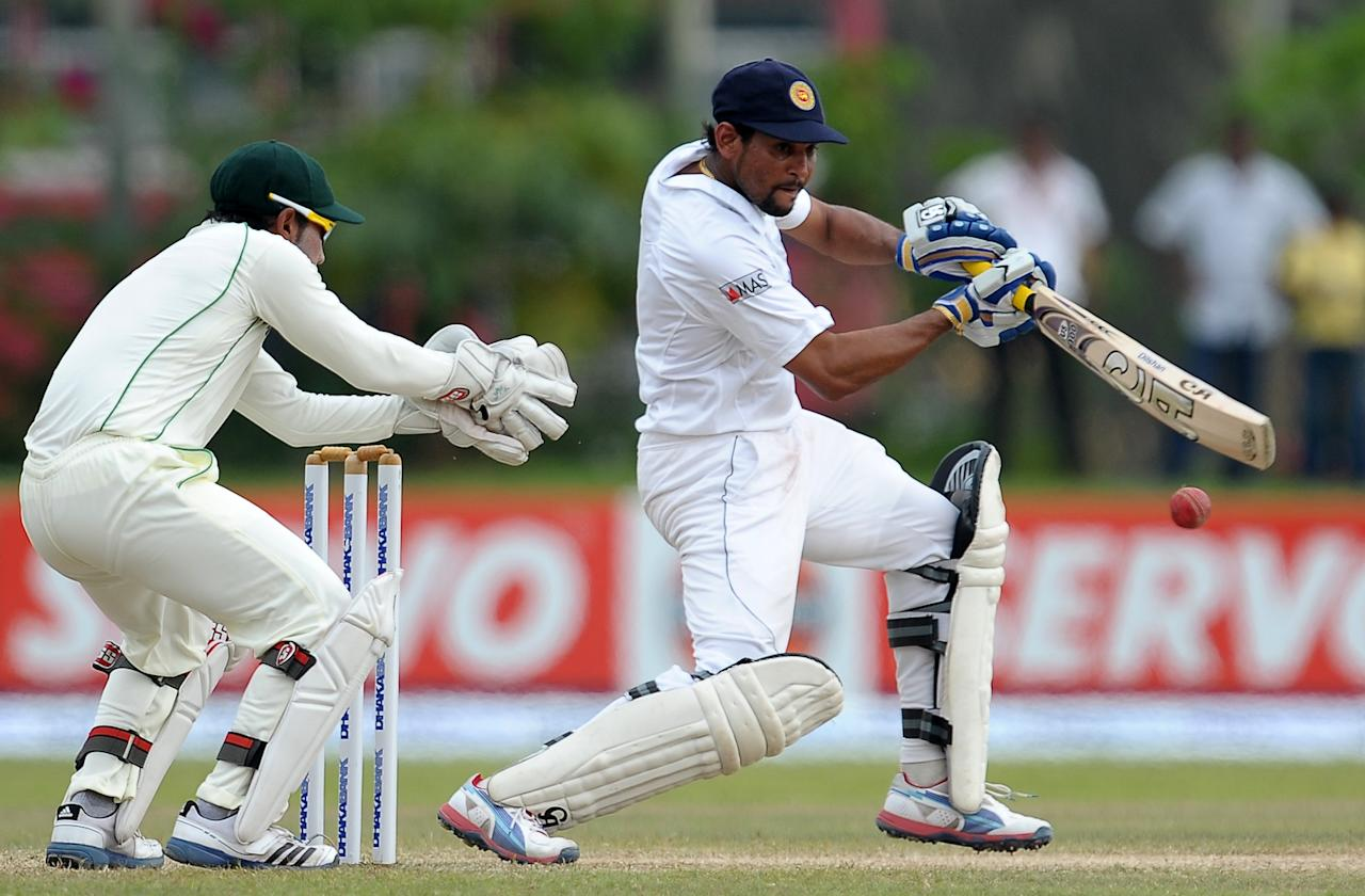 Sri Lankan batsman Tillakaratne Dilshan (R) plays a shot as Bangladeshi wicketkeeper and captain Mushfiqur Rahim look on during the fourth day of their opening Test match between Sri Lanka and Bangladesh at the Galle International Cricket Stadium in Galle on March 11, 2013. Bangladesh were bowled out for 638 in their first innings in reply to Sri Lanka's 570-4 declared on the fourth day of the opening Test in Galle on Monday. AFP PHOTO/ LAKRUWAN WANNIARACHCHI        (Photo credit should read LAKRUWAN WANNIARACHCHI/AFP/Getty Images)