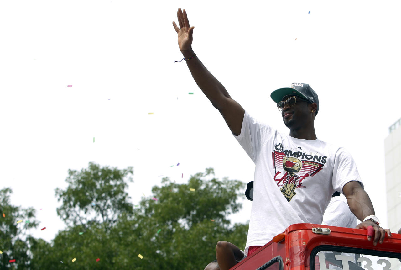 Miami Heat's Dwyane Wade waves from a double decker bus during a parade in celebration of winning the NBA Finals basketball championship against the Oklahoma City Thunder, Monday, June 25, 2012, in Miami. (AP Photo/Lynne Sladky)