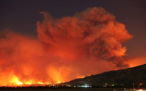 Smoke rises into the night sky as strong winds push the Thomas Fire across thousands of acres near Santa Paula - Credit: Reuters