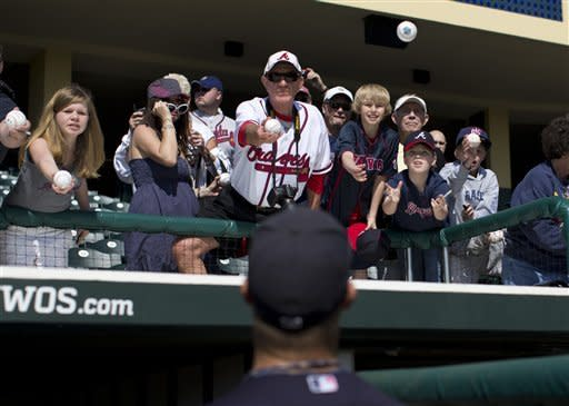 Fans reach out for autographs from Atlanta Braves catcher Evan Gattis before the start of an exhibition spring training baseball game against the New York Mets on Friday, March 15, 2013, in Kissimmee, Fla. (AP Photo/Evan Vucci)