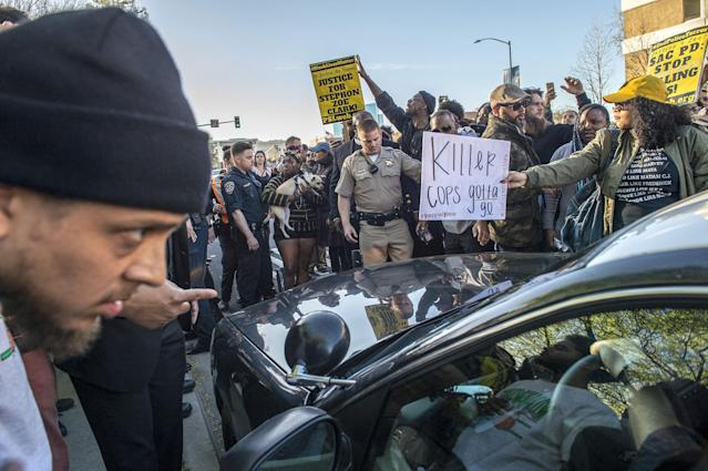 <p>Protesters surround a police car as they shut down Interstate 5 in both directions in downtown Sacramento, Calif., at the height of the afternoon commute on March 22, 2018. Protests erupted in Sacramento four days after Stephon Clark, an unarmed black man, was shot by police in his grandmother's backyard. Police said the officers who fired at Clark believed he had a gun. Investigators said they did not find a weapon, only a cell phone. (Photo:Renée C. Byer/Sacramento Bee via ZUMA Wire) </p>