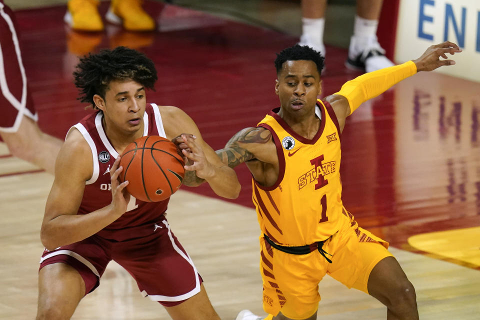 Oklahoma forward Jalen Hill passes ahead of Iowa State guard Tyler Harris, right, during the second half of an NCAA college basketball game, Saturday, Feb. 20, 2021, in Ames, Iowa. Oklahoma won 66-56. (AP Photo/Charlie Neibergall)