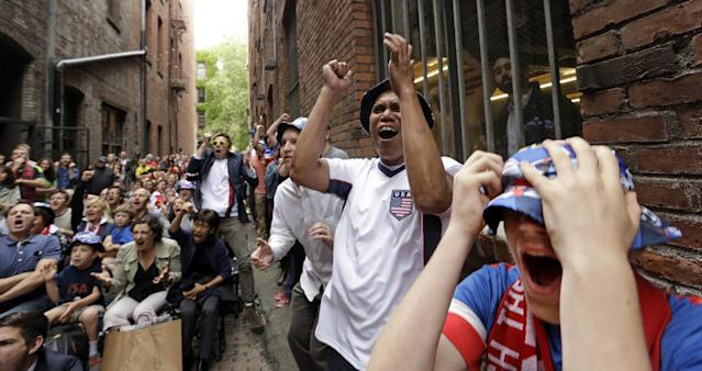 """Ethan Iano, right, Wil Cabatic, second from right, and Chris Draper react with other fans to a missed opportunity by the United States as they watch a World Cup soccer match between the U.S. and Germany Thursday, June 26, 2014, from an alley in Seattle's historic Pioneer Square neighborhood. """"Nord Alley"""" has been the site of large-screen viewing parties for World Cup games every match day. (AP Photo/Elaine Thompson)"""
