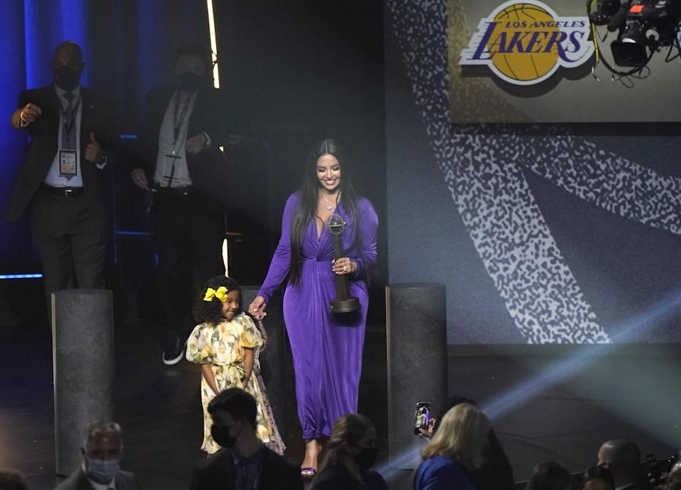 Bianka Bryant smiles for the crowd as her mother, Vanessa, holds Kobe Bryant's Hall of Fame trophy.