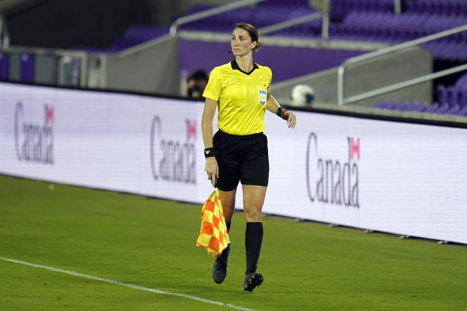 Assistant referee Kathryn Nesbitt runs the sideline as she watches play between Bermuda and Canada during the first half of a World Cup 2022 Group B qualifying soccer match, Thursday, March 25, 2021, in Orlando, Fla. Nesbitt, a 32-year-old from Philadelphia, had a breakthrough moment when she became the first woman to work as an on-field official for a World Cup qualifier in North and Central America and the Caribbean. (AP Photo/John Raoux)