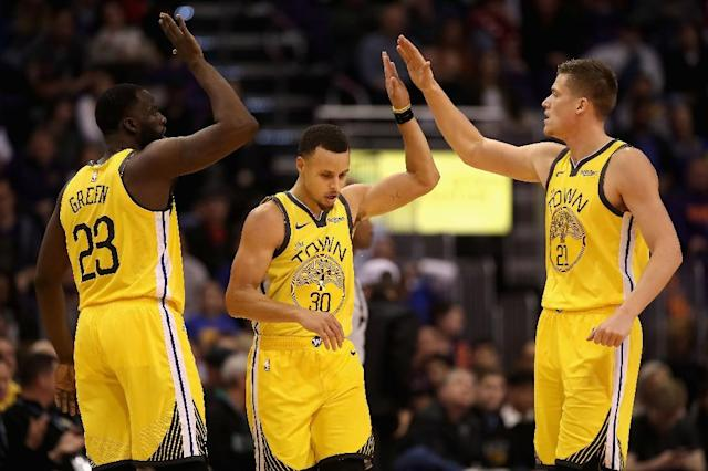 Draymond Green, Stephen Curry and Jonas Jerebko of the Golden State Warriors high-five on the way to an NBA victory over the Phoenix Suns (AFP Photo/Christian Petersen)