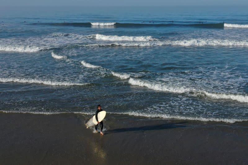 A surfer walks out of the Pacific Ocean at sunrise on the 50th anniversary of Earth Day, as the global outbreak of coronavirus disease (COVID-19) continues, in Huntington Beach