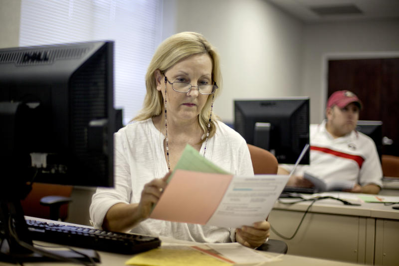 "In this Aug. 22, 2012 photo, Judy Smith, of Dalton, Ga., looks over paperwork as she files for unemployment for the first time since being laid off from a catering job at a convention center in Dalton, Ga. Collapsing industry or not, Dalton city officials are still the proud owners of the label ""Carpet Capital of the World,"" but what they aren't happy about is the most recent label: The city that is leading the nation in the number of job losses per capita this year. The city that makes nearly 75 percent of the nation's flooring has lost 4,600 jobs between June 2011 and June 2012 according to the United States Bureau of Labor Statistics. Dalton's economy hit bottom in 2009 with the collapse of the housing market, taking hundreds of distributor business and support services down with it and struggling to recover in recent years. (AP Photo/David Goldman)"