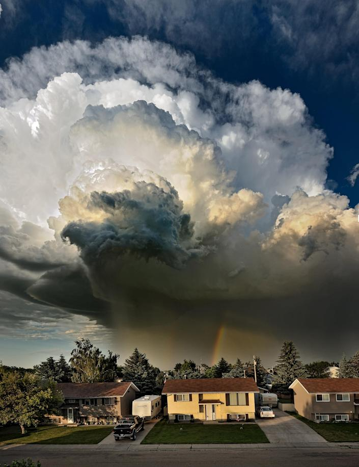 This is the terrifying moment a cloud threatened to develop into a full blown TORNADO over a row of family homes. Brave snapper Pat Kavanagh took this shot of an explosive black storm from the roof of his house in Taber, Canada last month. Expecting the sunny weather to take a turn for the worse he watched intently as the billows started spinning into a furious funnel. This pic was created by stitching together multiple photographs in a vertical panorama. (Photo: PAT KAVANAGH / CATERS NEWS)