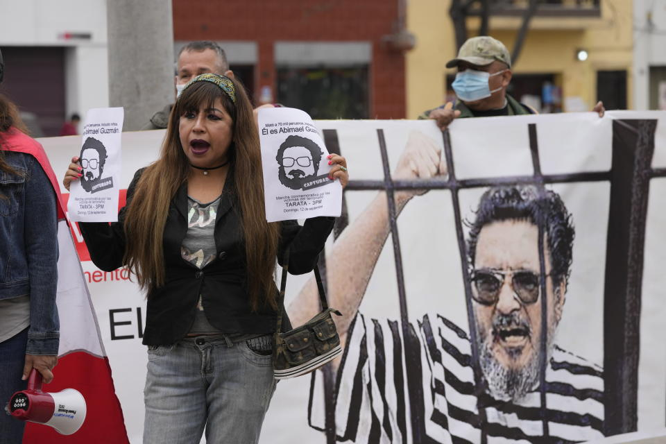 People gather outside the anti-terrorism directorate to celebrate the death of Abimael Guzman, founder and leader of the Shining Path guerrilla movement, in Lima, Peru, Saturday, Sept. 11, 2021. Guzman, who was captured in 1992, died on Saturday in a military hospital after an illness, the Peruvian government said. He was 86. (AP Photo/Martin Mejia)