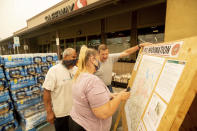 As new evacuation orders take effect for the Dixie Fire, residents examine a fire map in Quincy, Calif., on Sunday, July 25, 2021. From right to left are Rich McFeely, Vickie Duran and Carlos Duran. (AP Photo/Noah Berger)