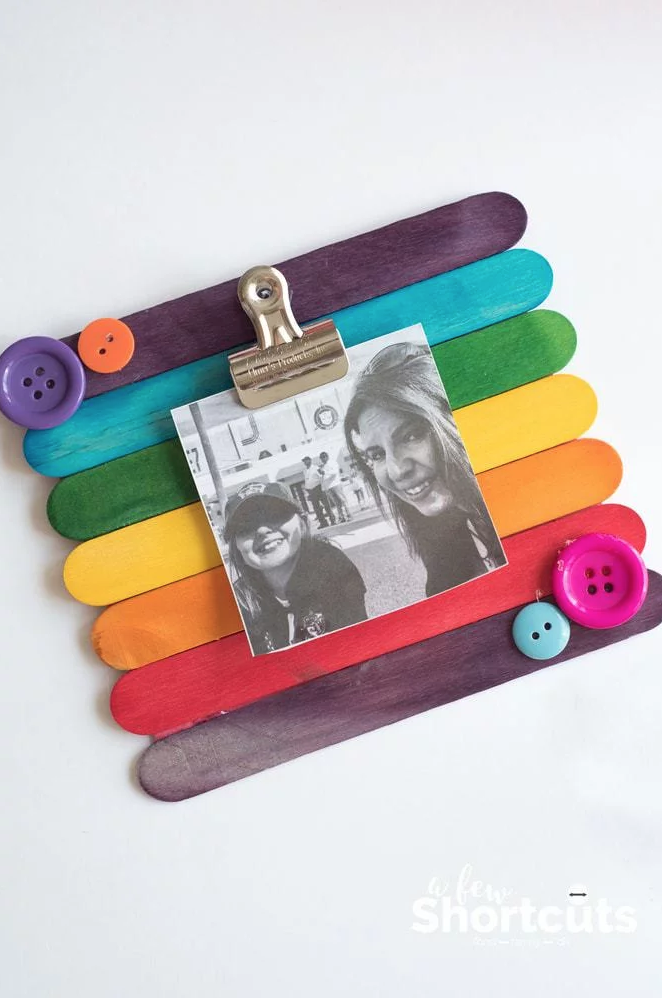 """<p>Once the kids have picked out their favorite photo with Mom, they can proudly display it against a handmade frame. The brighter, the better!</p><p><strong>Get the tutorial at <a href=""""https://afewshortcuts.com/diy-popsicle-stick-picture-frame-kids-craft/"""" rel=""""nofollow noopener"""" target=""""_blank"""" data-ylk=""""slk:A Few Shortcuts"""" class=""""link rapid-noclick-resp"""">A Few Shortcuts</a>. </strong></p><p><strong><a class=""""link rapid-noclick-resp"""" href=""""https://www.amazon.com/Korlon-Sticks-Wooden-Popsicle-Length/dp/B01EFGEIR0/?tag=syn-yahoo-20&ascsubtag=%5Bartid%7C10050.g.4233%5Bsrc%7Cyahoo-us"""" rel=""""nofollow noopener"""" target=""""_blank"""" data-ylk=""""slk:SHOP POPSICLE STICKS"""">SHOP POPSICLE STICKS</a><br></strong></p>"""