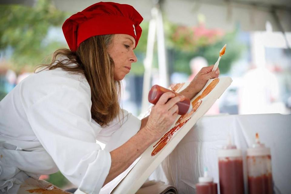 """Cynthia Kostylo, of Lexington, Ky., paints with Heinz ketchup during Ketchup Art on the Green at The Summit at Fritz Farm in Lexington, Saturday, July 31, 2021. Kostylo says that ketchup is a similar medium to standard paint but the final product is temporary, """"So it's just playing with food,"""" She said."""