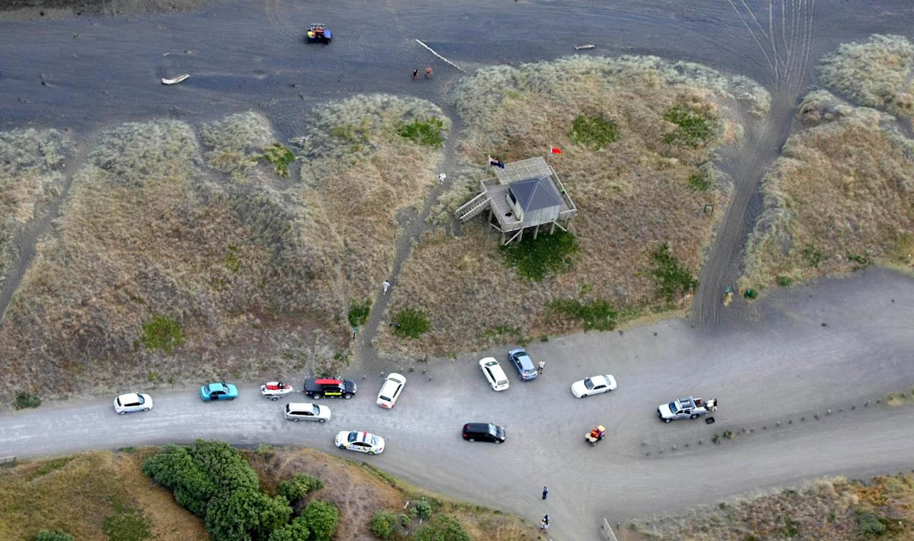 "In this aerial photo, emergency vehicles are parked at Muriwai Beach near Auckland, New Zealand, Wednesday, Feb. 27, 2013, following a fatal shark attack. Police said a man was found dead in the water Wednesday afternoon after being ""bitten by a large shark."" Police and surf lifesavers recovered the man's body. The police statement said Muriwai Beach near the city of Auckland has been closed. (AP Photo/New Zealand Herald, Chris Gorman) NEW ZEALAND OUT, AUSTRALIA OUT"
