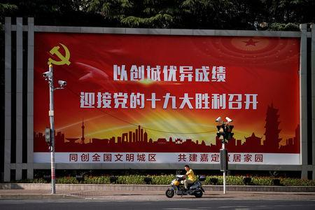 A man rides an electric scooter past a poster, promoting the 19th National Congress of the Communist Party of China (CPC) in Shanghai, China September 14, 2017. REUTERS/Aly Song