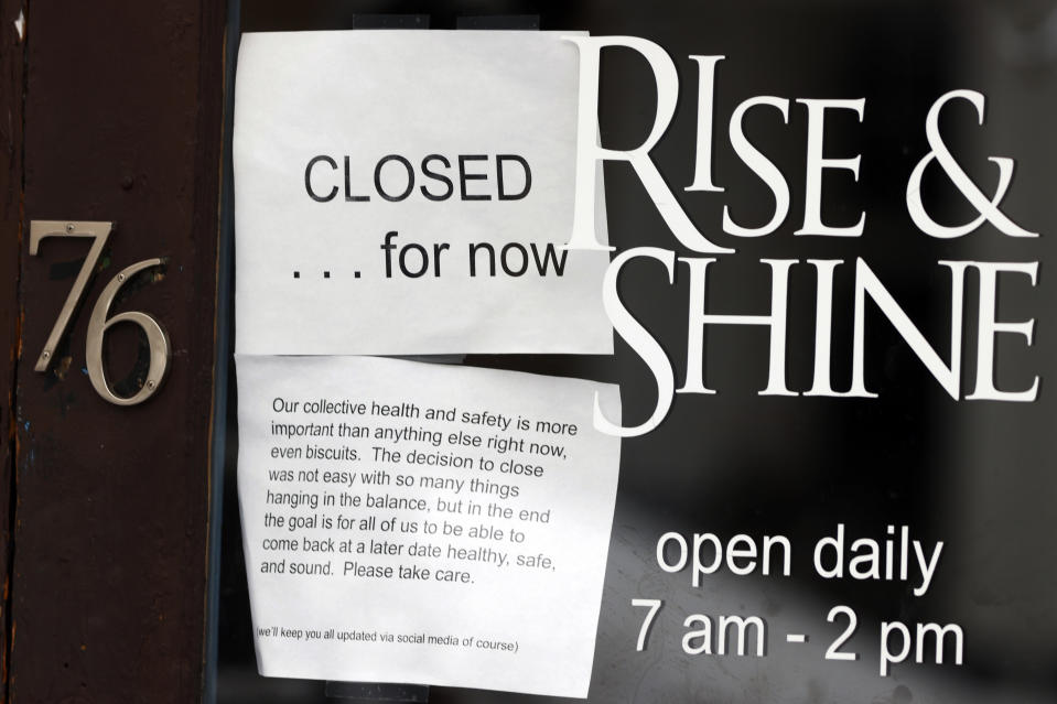 FILE - This April 16, 2020, file photo shows a closed sign hanging in the window of a coffee house since a statewide stay-at-home order was put into effect to stop the spread of the new coronavirus in Denver. Colorado's unemployment rate rose sharply to 4.5% in March, and a much bigger spike is expected as the state economy slows even more amid the coronavirus pandemic, officials said in a report Friday, April 17, 2020. (AP Photo/David Zalubowski, File)