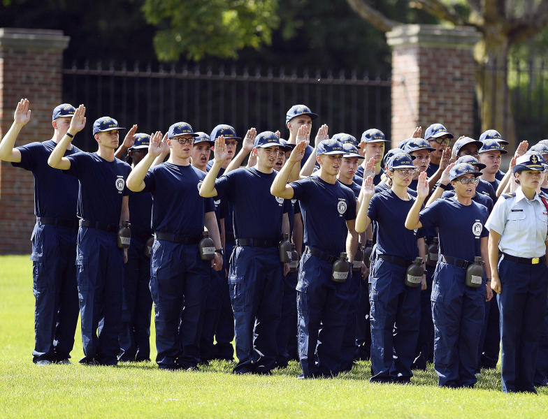 "FILE — In this July 1, 2019 file photo, members of the U.S. Coast Guard Academy Class of 2023 take their oath of office on the first day of Swab Summer in New London, Conn. The school, like other service academies and military training centers, has made major changes because of the coronavirus pandemic. That means the eight weeks of boot camp for new cadets, known as ""Swab Summer,"" will be much different. There will be no haircuts, no drilling, no running as a group from place to place, no lining up against the wall in the hall of the barracks for pushups. (Sean D. Elliot//The Day via AP, File)"