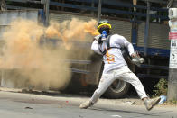"""FILE - In this March 27, 2021, file photo, an anti-coup protester throws a smoke bomb against police during a crackdown in Thaketa township in Yangon, Myanmar. Former United Nations Secretary General Ban ki-Moon is urging the world body and Southeast Asian countries to take swift and """"strong action"""" to stop the deadly crackdown that has followed a military coup in Myanmar. (AP Photo/File)"""