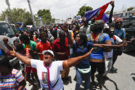 Supporters of former Haitian President Jean-Bertrand Aristide celebrate his arrival from Cuba, where he underwent medical treatment, in Port-au-Prince, Haiti, Friday, July 16, 2021. President Jovenel Moise was assassinated at his residency on July 7. (AP Photo/Fernando Llano)