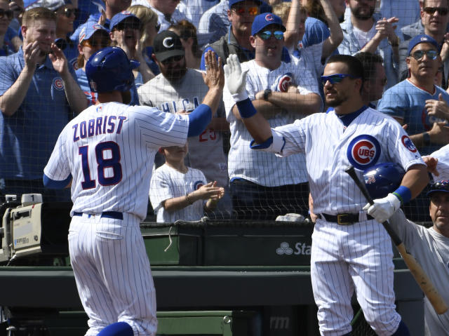 Chicago Cubs' Ben Zobrist (18) is greeted by Kyle Schwarber (12) after scoring against the Pittsburgh Pirates during the second inning of a baseball game, Monday, April 8, 2019, in Chicago. (AP Photo/David Banks)