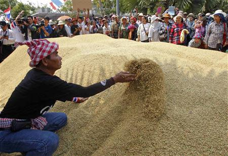 Farmers rearrange a pile of rice after dumping them on the ground during a rally demanding the Yingluck administration resolve delays in payment from the rice pledging scheme, outside a Bank for Agriculture and Agricultural Cooperatives in Bangkok March 11, 2014. REUTERS/Chaiwat Subprasom