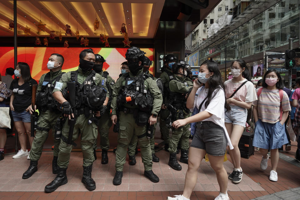 Pedestrians pass police standing guard during China's National Day in Causeway Bay, Hong Kong, Thursday, Oct. 1, 2020. A popular shopping district in Causeway Bay saw a heavy police presence the Oct. 1 National Day holiday despite low protester turnout. (AP Photo/Kin Cheung)
