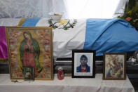 Religious images and a portrait are placed next to coffin with the remains of Rubelsy Tomas Isidro, one of the Guatemalan migrants who was killed near the U.S.-Mexico border in January, during a wake at his home in Comitancillo, Guatemala, Saturday, March 13, 2021. Thousands of residents of this Guatemalan town turned out Friday night amid tears and applause to receive the remains of 16 of their own, found piled in a charred pickup truck in Camargo, across the Rio Grande from Texas. (AP Photo/Moises Castillo)