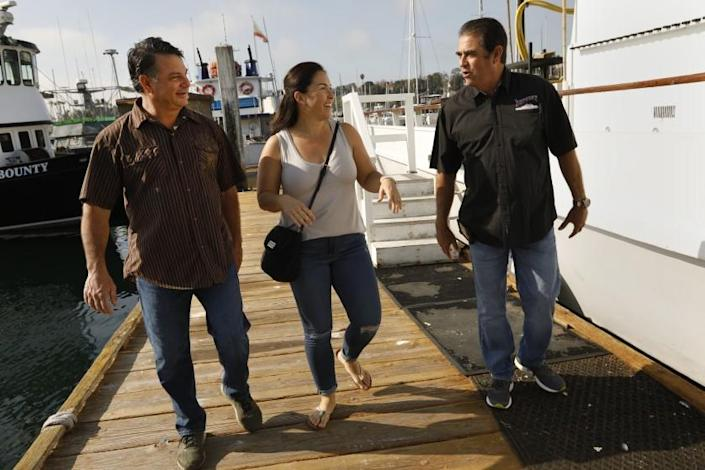 San Pedro, California-Desiree Rodriguez, center, together with Mark Pisano, left, and Paul Strasser, right, who rescued her after a boating accident off of Catalina Island in 1986 when she was only 9-years-old. Rodriguez, who is now an L.A. County sheriff's deputy, survived after hours in the ocean with only her lifejacket. Photos taken at 22nd Street Landing in San Pedro, California on Feb. 7, 2021. (Carolyn Cole/Los Angeles Times)