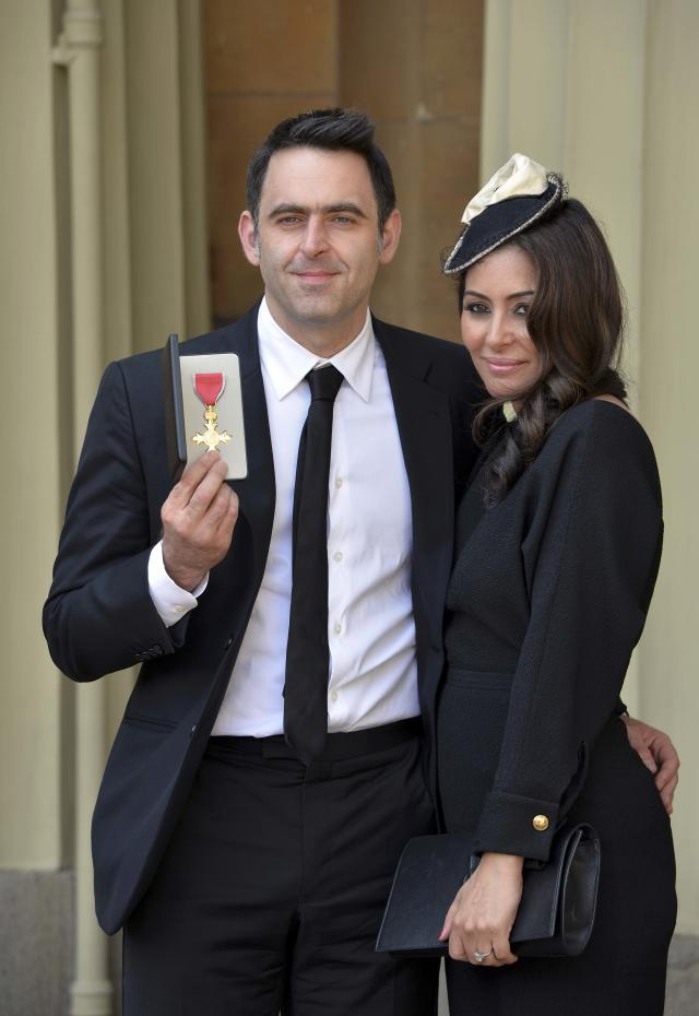 Snooker player Ronnie O'Sullivan poses with his partner Laila Rouass after receiving an OBE from the Prince of Wales at an investiture ceremony at Buckingham Palace in London, Britain May 6, 2016. REUTERS/John Stillwell/Pool