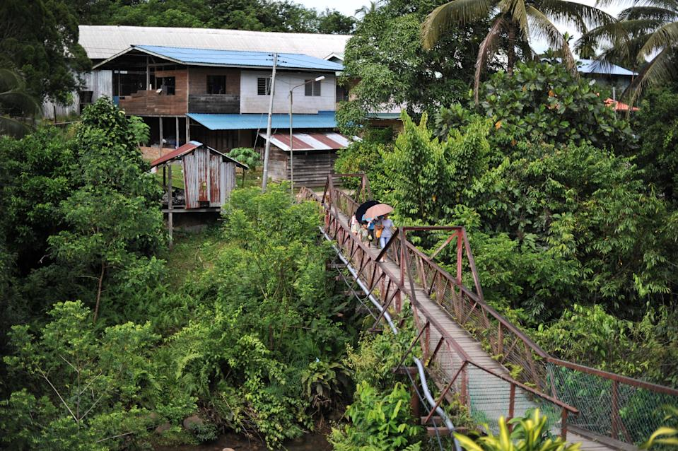 <p>File image: Villagers walk on a bridge in Malaysia's Sarawak state on Borneo island</p> (AFP via Getty Images)