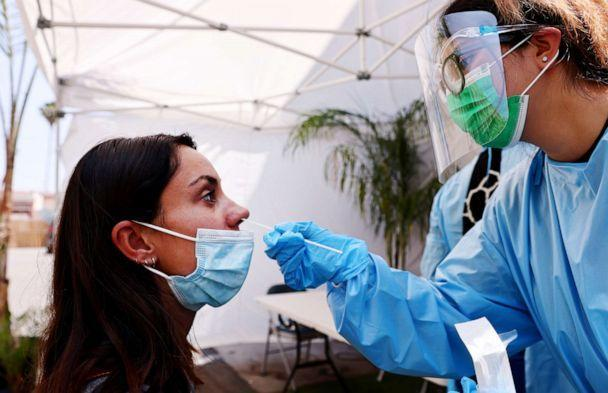 PHOTO: A registered nurse administers a COVID-19 test to a person at Sameday Testing on July 14, 2021, in Los Angeles. (Mario Tama/Getty Images)