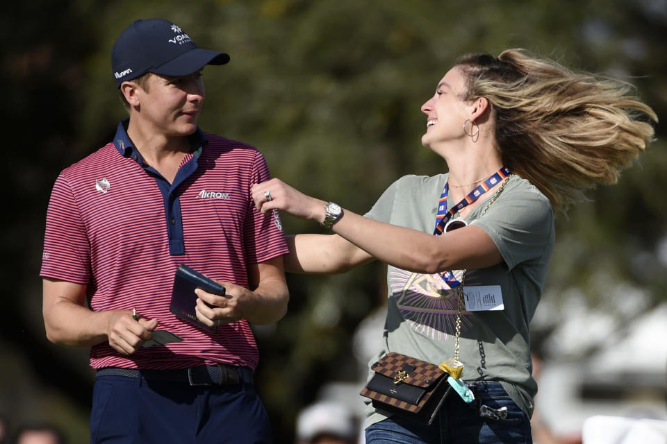 Haley Ortiz, left, runs onto the 18th green to greet her husband, Carlos Ortiz, after Carlos won the Houston Open golf tournament, Sunday, Nov. 8, 2020, in Houston. (AP Photo/Eric Christian Smith)
