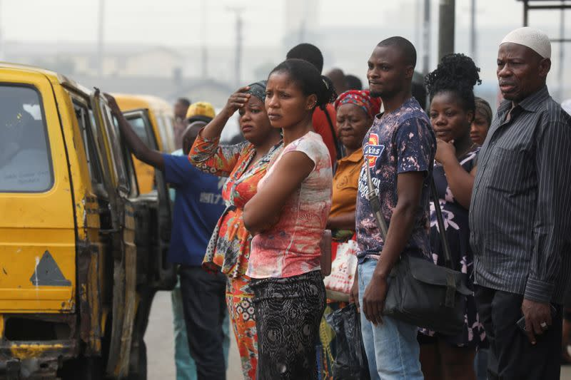 People are seen waiting for a bus at a bus-stop in Lagos