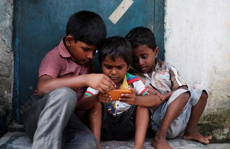 FILE PHOTO: Children play a game on a mobile phone at slum area in New Delhi