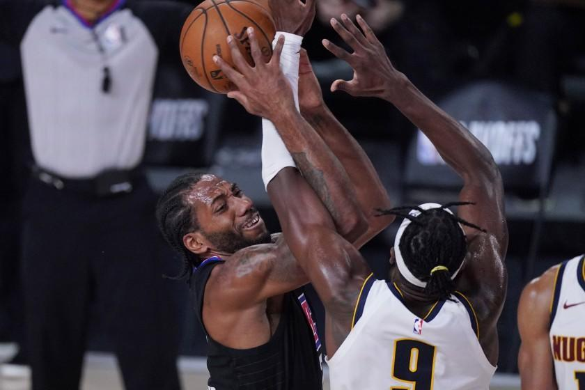 Los Angeles Clippers forward Kawhi Leonard (2) is defended by Denver Nuggets forward Jerami Grant (9) as he tries to score during the second half of an NBA conference semifinal playoff basketball game Tuesday, Sept. 15, 2020, in Lake Buena Vista, Fla. (AP Photo/Mark J. Terrill)