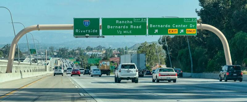 Guide signs on large overhead signage informing drivers about the intersections and highways, and distance and directions to destinations - Riverside, California, USA - April 22, 2019
