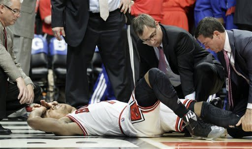 Chicago Bulls guard Derrick Rose (1) is helped by trainers after an injury during the fourth quarter of Game 1 in the first round of the NBA basketball playoffs against the Philadelphia 76ers in Chicago, Saturday, April 28, 2012. The Bulls won 103-91. (AP Photo/Nam Y. Huh)