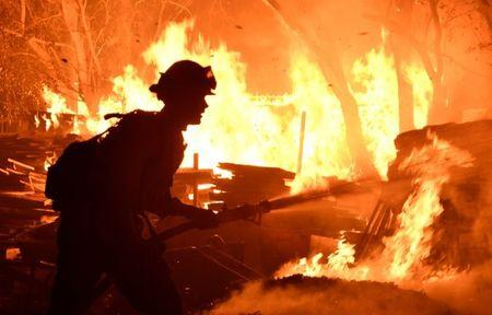 Santa Barbara County firefighters battle flames at a home at the site of a wildfire in Goleta
